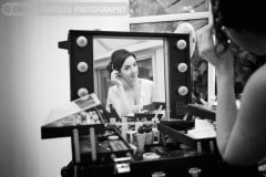 a bridesmaid checks her appearance in a mirror. Black and white wedding photography