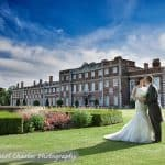 Bride and groom in gardens of Knowsley Hall with hall and fountain in background