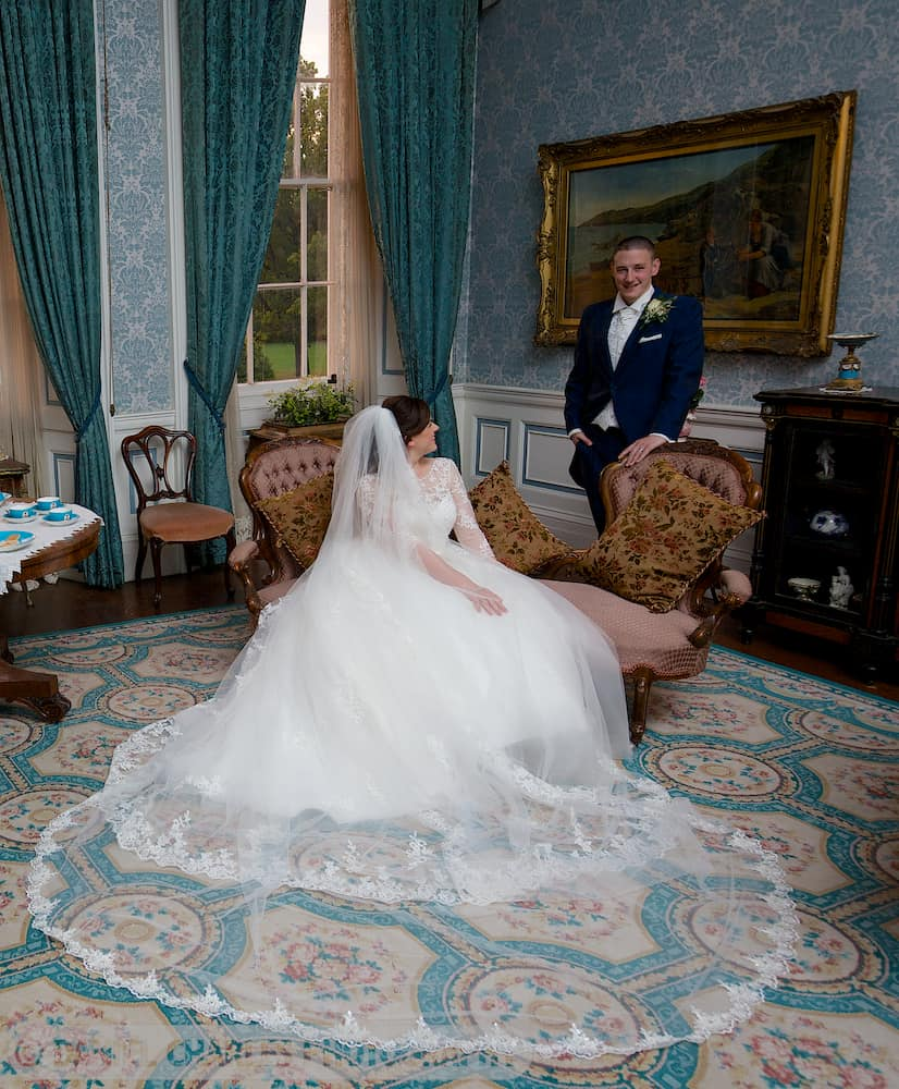 bride seated on chaise lngue with groom in background croxteth hall wedding photography