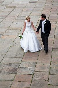 bride and groom walking hand in hand on sandstone slabs of plaza by st georges hall. Image by liverpool wedding photographer daniel charles photography