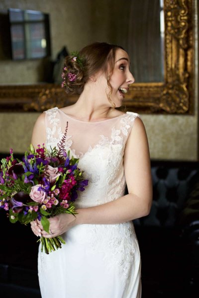 a bride looks over her shoulder, laughing