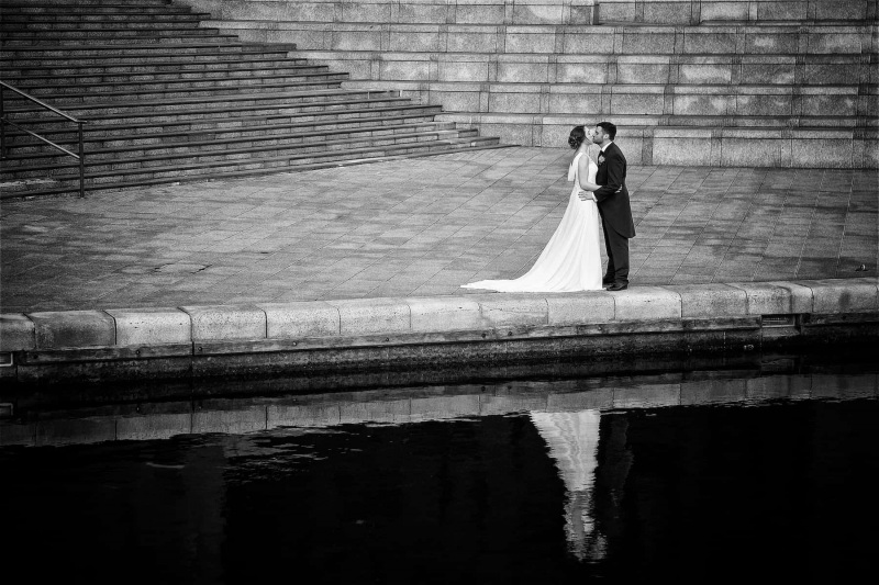 A bride and groom are kissing, reflected in Liverpool dock water in this  black and white wedding photograph