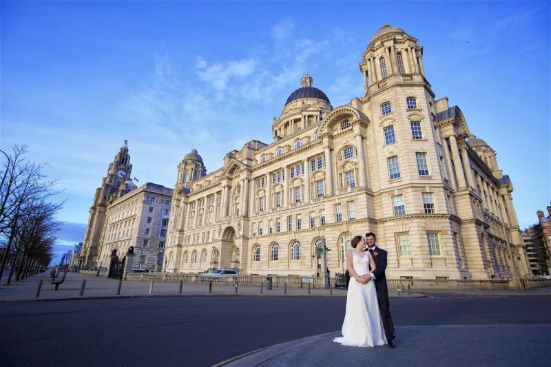 A bride and groom are standing in front of the Port of Liverpool Building on a bright spring day with blue sky
