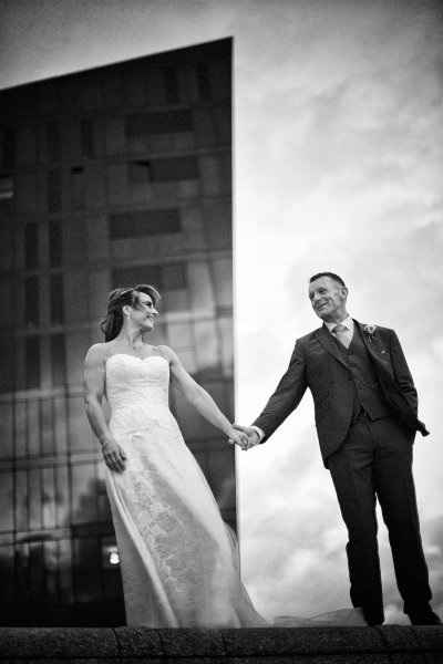 a bride and groom are holding hands, looking at each other, in this black and white  liverpool wedding photo