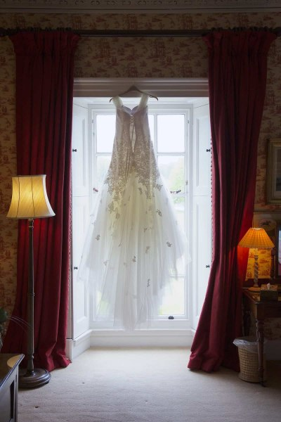 wedding dress hanging up in window at knowsley hall