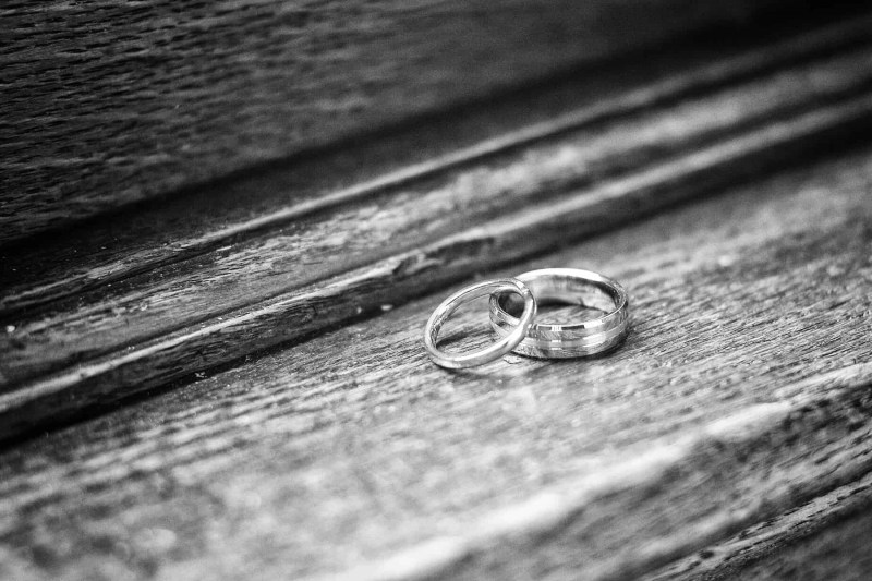 black and white wedding photography of rings on a window sill