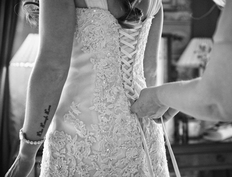 a wedding dress being done up. Black and white wedding photograph