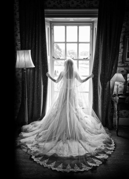 black and white wedding photograph of bride standing in front of window in knowsley Hall