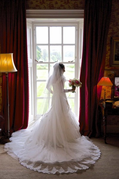 bride standing in front of window in knowsley Hall