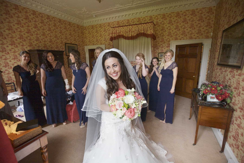 bride laughing asa her bridesmaids see her in dress for the first time