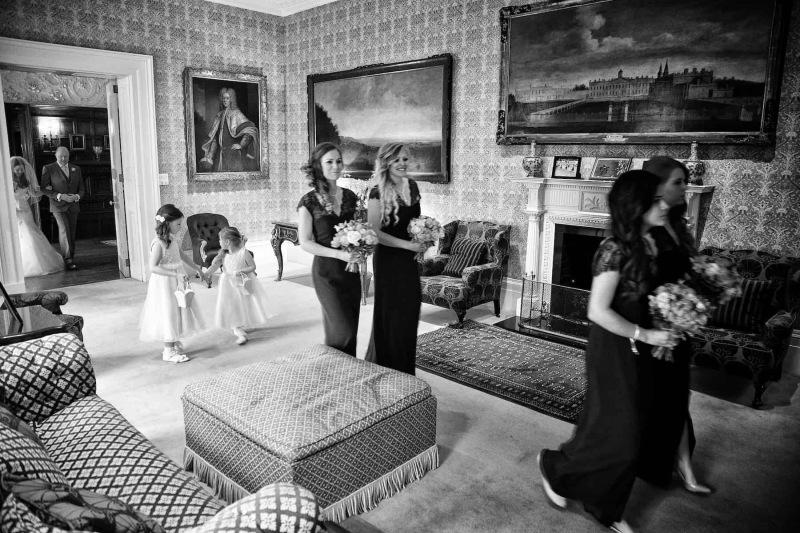bridesmaids walking through green drawing room at Knowsley Hall