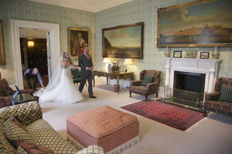 a staff member assists the bride as she walks through the Green Drawing Room of Knowsley Hall