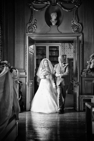 black and white wedding photograph of bride and dad entering Stucco Ballroom at Knowsley Hall