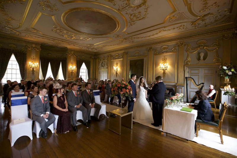 a wide shot of Knowsley Hall's stucco ballroom with a wedding in progress