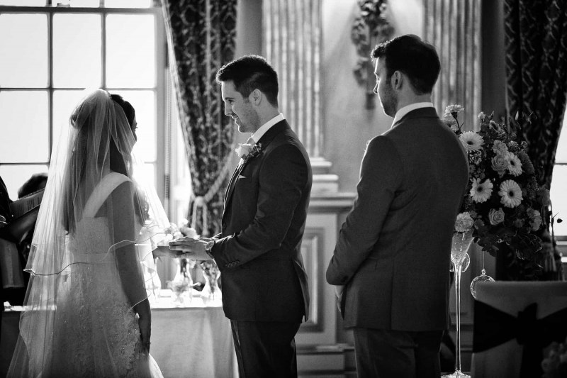 black and white photo of groom smiling at bride as he puts her ring on her finger