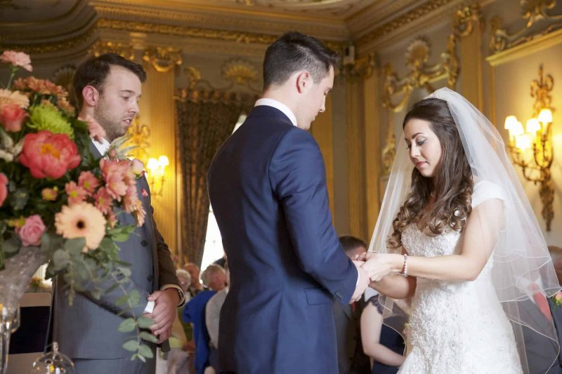 bride places groom's  ring on his  finger