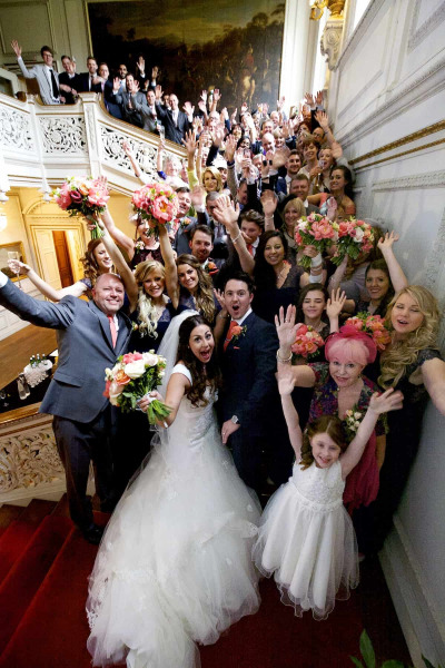 wedding guests waving at camera from Grand Staircase Knowsley Hall