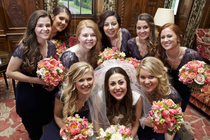 bridesmaids grouped close together all looking at camera