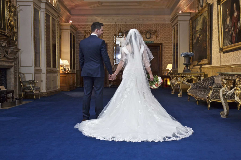 bride and groom walking hand in hand through the Library, Knowsley Hall