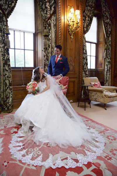 bride seated with groom standing in walnut drawing room, knowsley hall