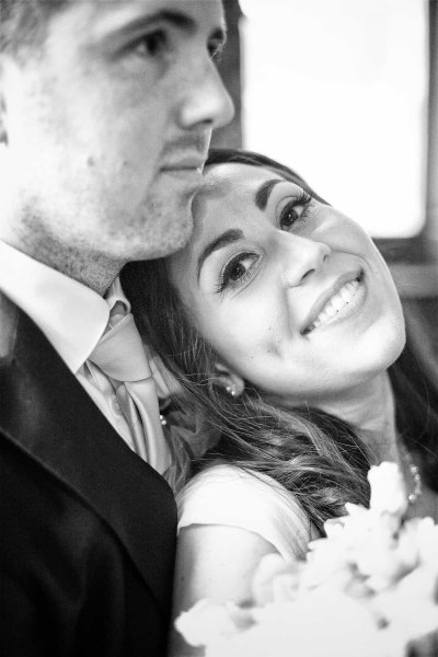 bride smiling at camera with groom looking off to the right