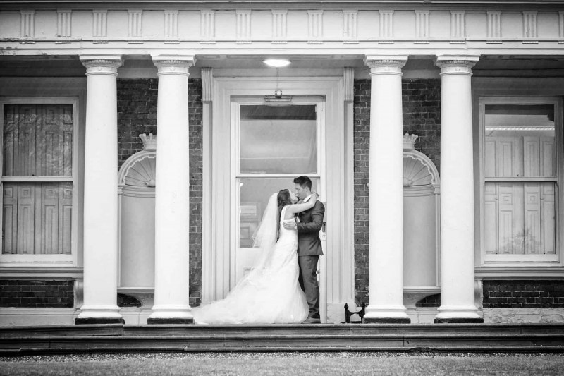 bride and groom at side of knowsley hall, black and white wedding photograph
