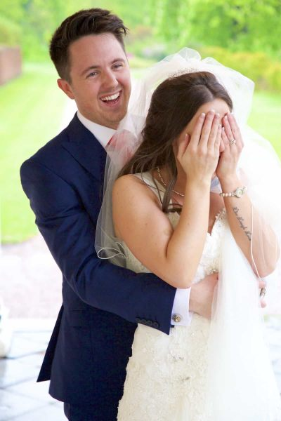 bride covers her face with her hands after groom whispers in her ear