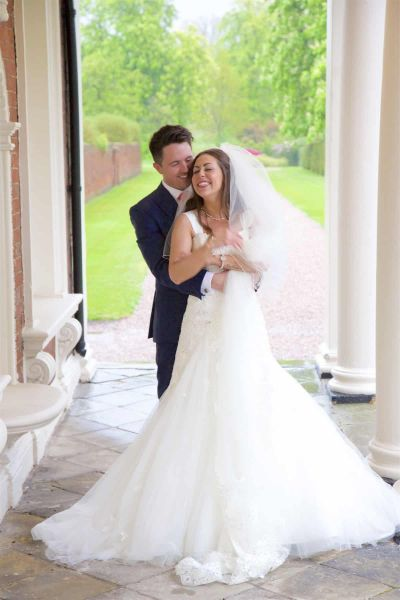 groom whispers in bride's  ear in knowsley hall exterior colonnade