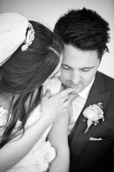 bride tenderly touches grooms face in black and white wedding photograph