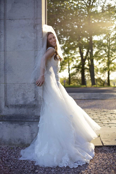 bride leaning against wall in knowsley hall gardens