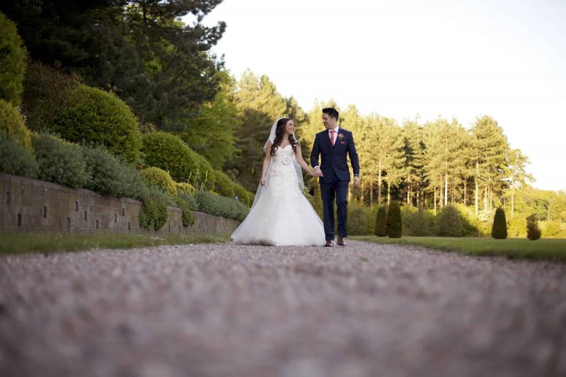 bride and  groom walking hand in hand in knowsley hall wedding photograph