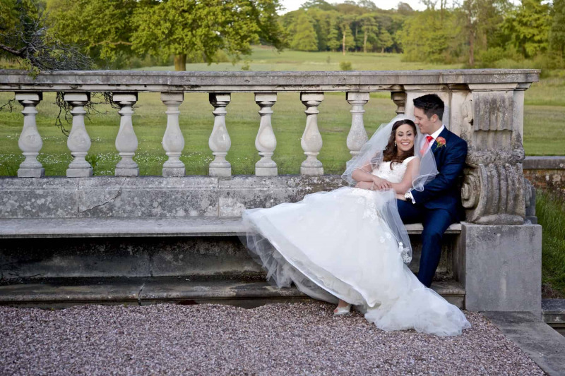 bride and  groom reclining on stone bench at knowsley hall