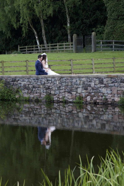 bride and groom seated on wall overlooking pond with their reflection visible