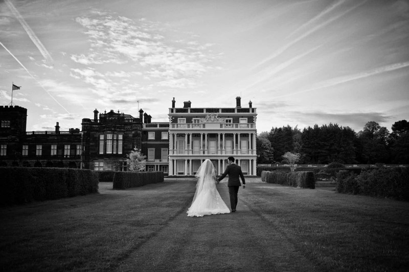 bride and groom walking in knowsley hall gardens