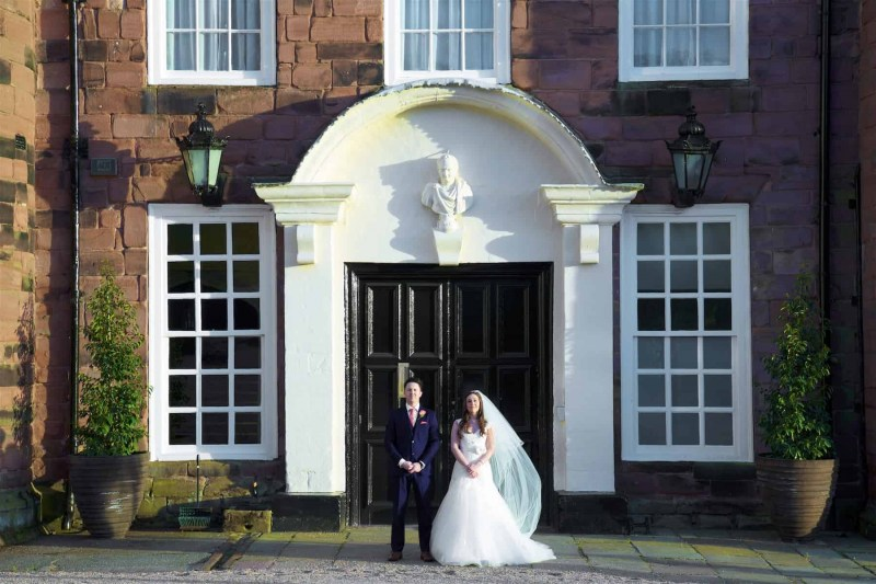 bride and groom standing by doorway of knowsley hall