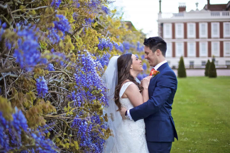 bride and groom embracing by lilac bush