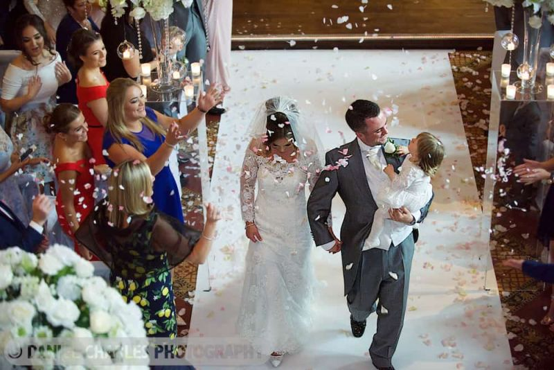 bride and groom walking down aisle with confetti cheshire wedding photographer