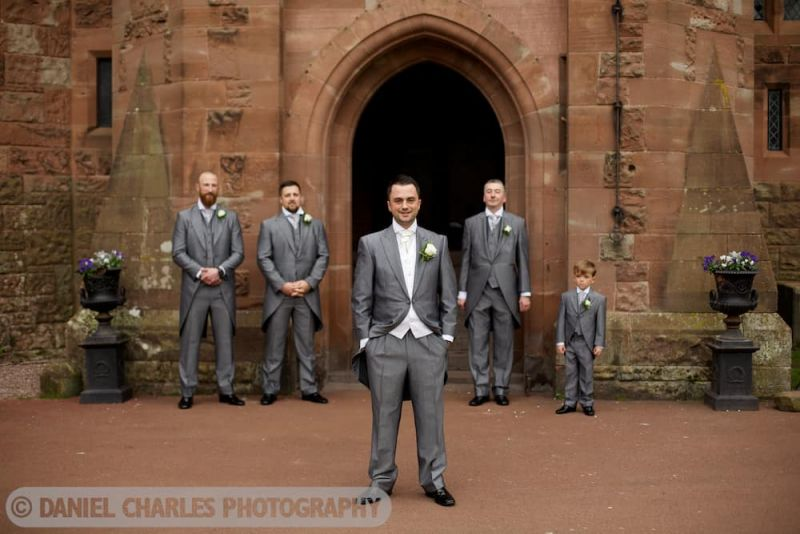 groom and groomsmen standing outside front door of peckforton castle