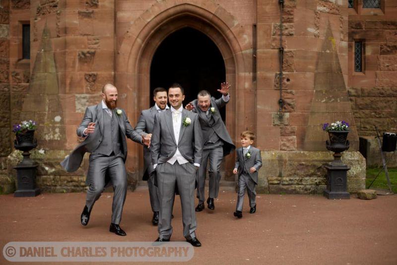 groomsmen run towards groom at peckforton castle