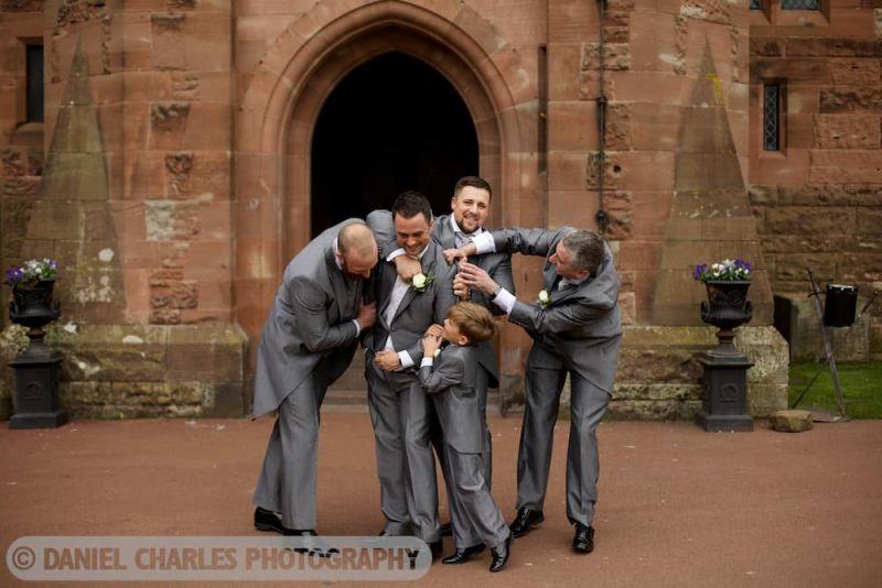 groomsmen grab hold of groom