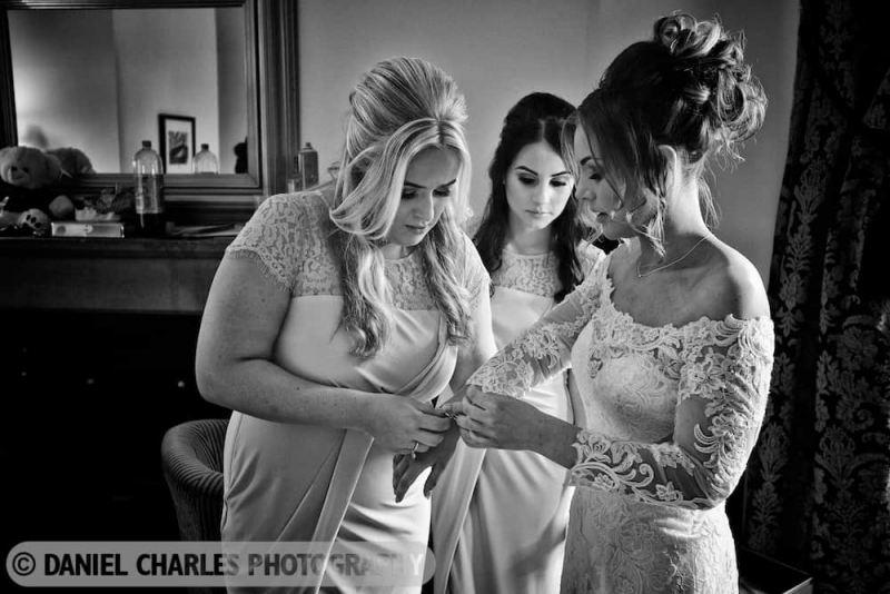 bridesmaid helping bride with bracelet