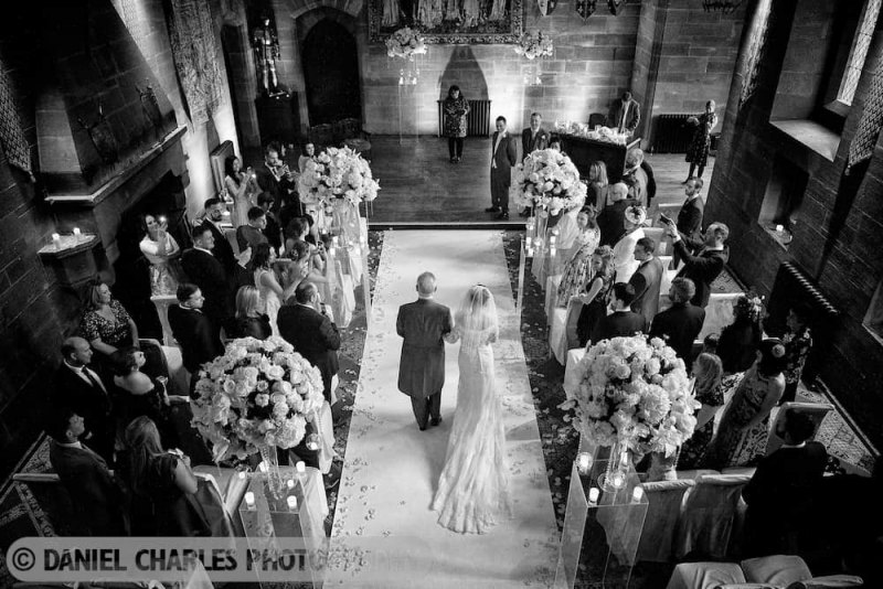 the bride and her father enter the wedding ceremony room at peckforton castle