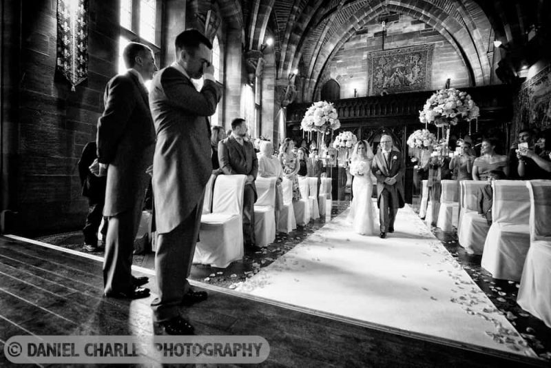 groom crying as bride and her father approach him down the aisle of Peckforton Castle