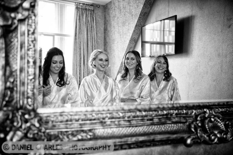 black and white photo of bridesmaids smiling in mirror