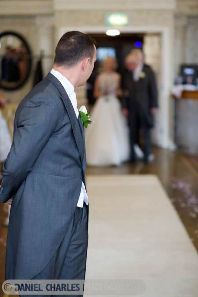 groom turns to watch approach of bride and father