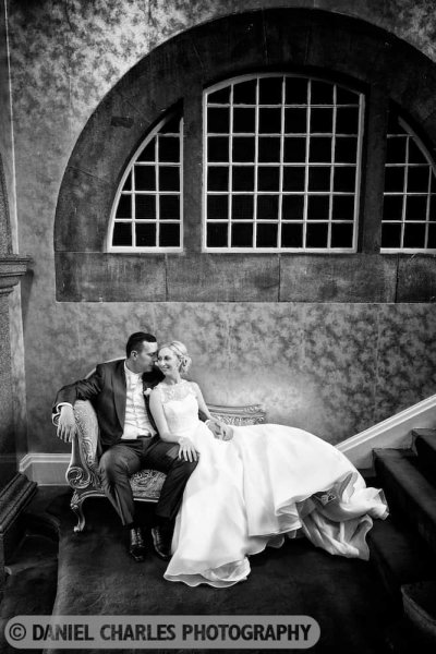 bride and groom seated on chaise longue