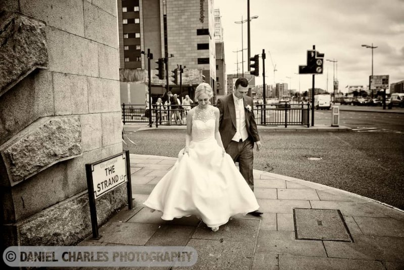 sepia tone photo of bride and groom walking on the strand liverpool