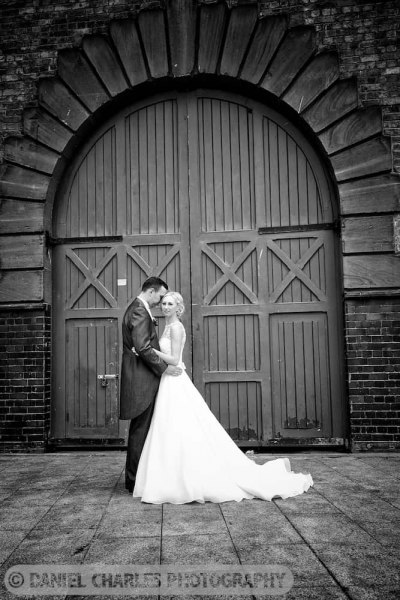 bride and groom standing in front of gates