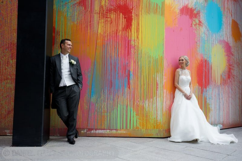 bride and groom in front of splashed paint