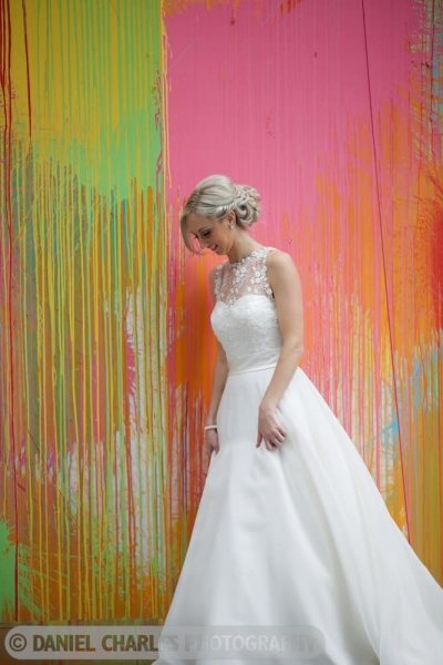 bride stands in front of splashed paint background